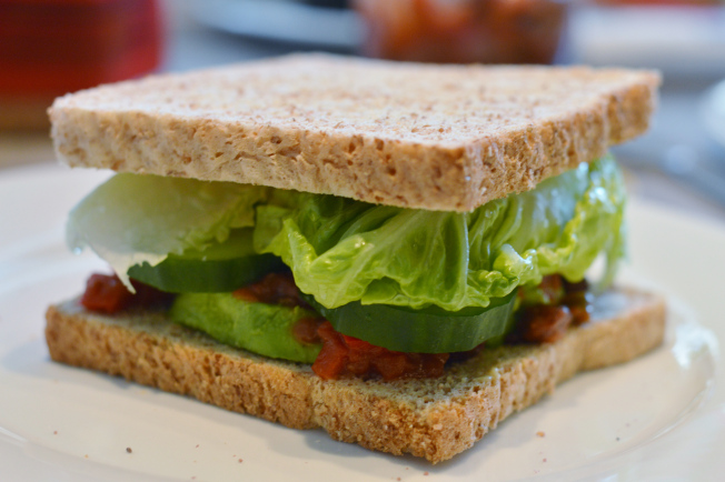zwei Sandwiches mit Avocado, Kala Namak, Mandelmus, Salsa, Kidney Bohnen, Gurken und Salat.