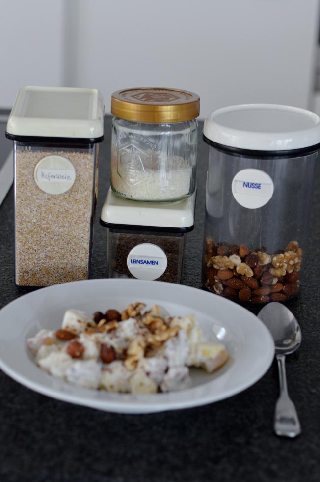 Sojajoghurt mit Äpfeln. Verfeinert habe ich das noch mit Kokosflocken, Leinsamen, Nüssen und Haferkleie
