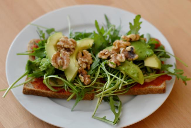 Pizzatoast mit Tomatensauce, Mandelmus, Kräutern, Rucola, Avocado und Walnüssen