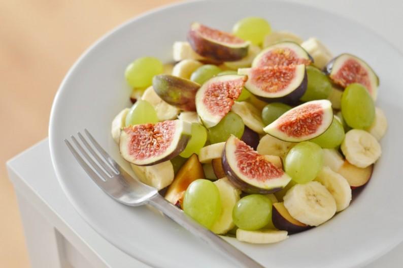 Obstteller mit Banane, Birne, Pflaume, Trauben und einer Feige